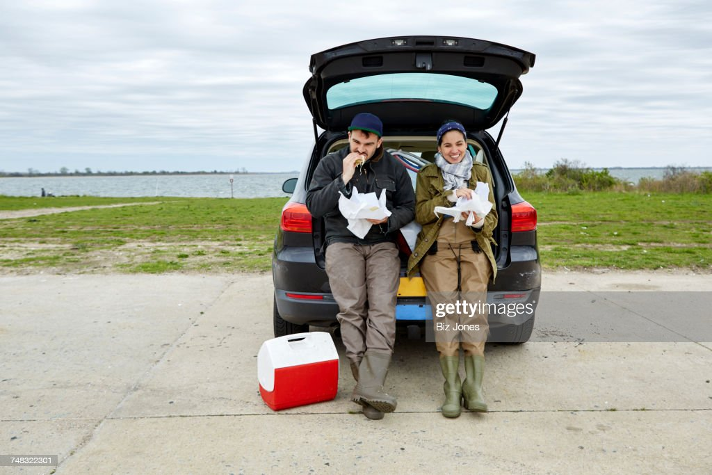 Young couple sitting in open car boot, eating food from paper : Stock Photo