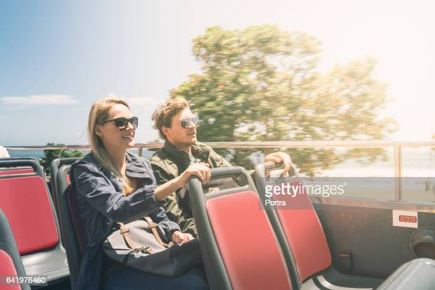 young couple sitting in open-air bus on sunny day - double decker bus stock pictures, royalty-free photos & images