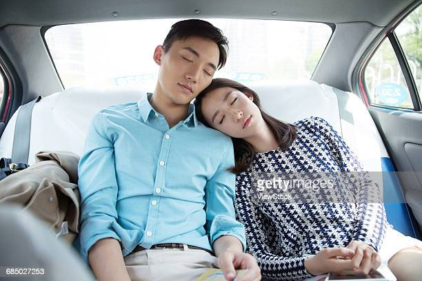 Young couple sitting in the car to sleep