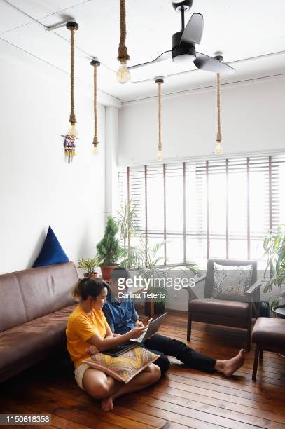 young couple sitting in the floor reading from a laptop - heterosexual couple stock pictures, royalty-free photos & images