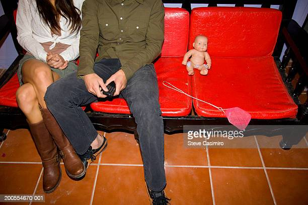 young couple sitting indoors with fly swatter and baby doll, low section, elevated view - woman straddling man stock pictures, royalty-free photos & images