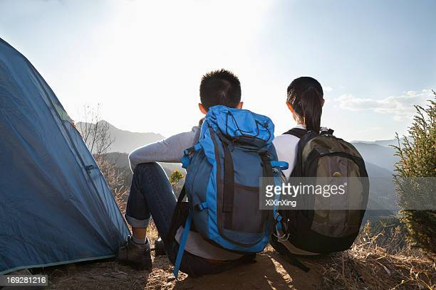 Young couple sitting next to the tent