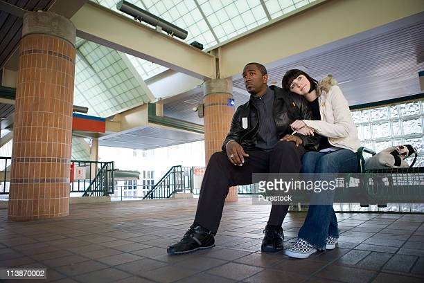 Young couple sitting on a bench at a public train station