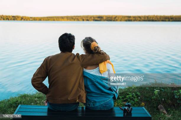 young couple sitting on a bench, looking at the lake - norrbotten province stock pictures, royalty-free photos & images