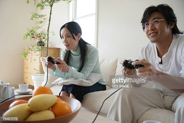 Young couple sitting on a couch and playing video games