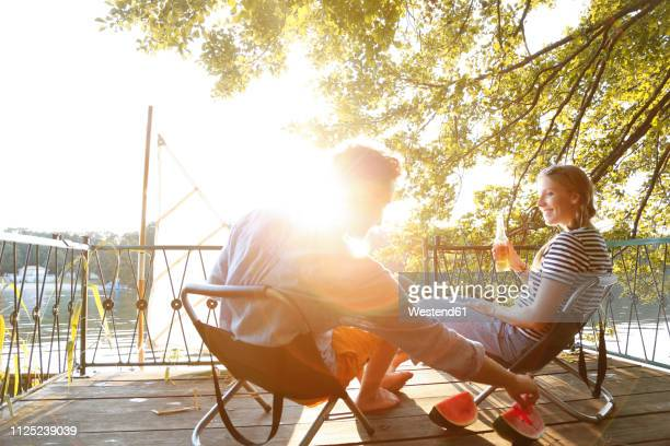 young couple sitting on a jetty at a lake eating watermelon - gegenlicht stock-fotos und bilder
