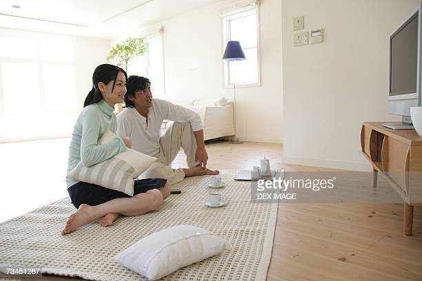 Young couple sitting on a mat and watching television