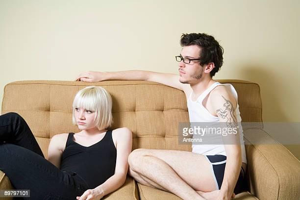 a young couple sitting on a sofa - côte à côte photos et images de collection