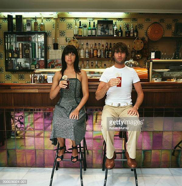 Young couple sitting on bar stools holding drinks, portrait