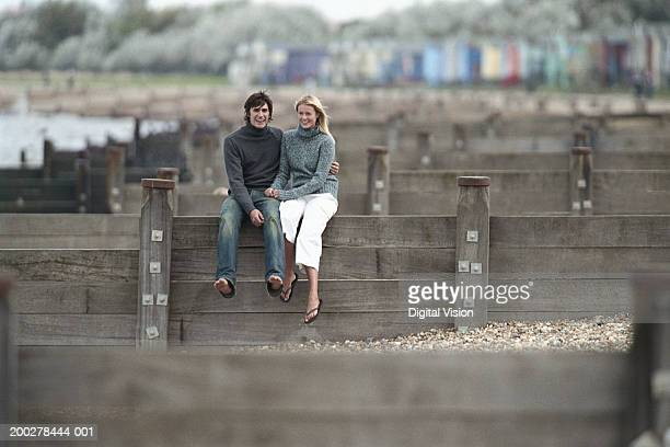 Young couple sitting on beach groyne, smiling, portrait of man