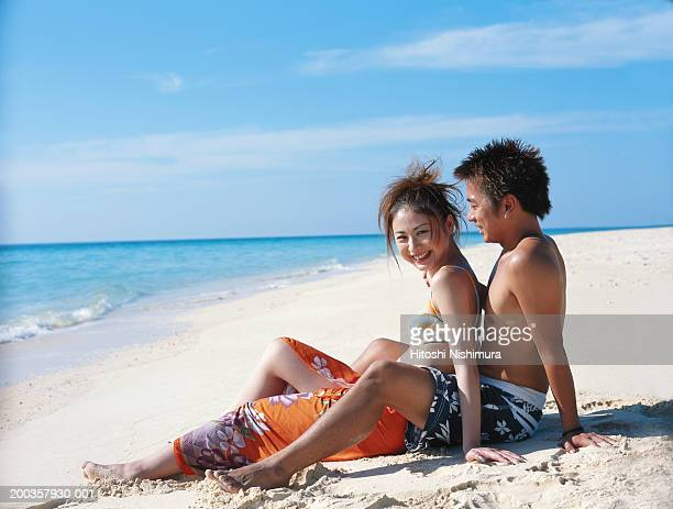 Young couple sitting on beach, smiling, side view
