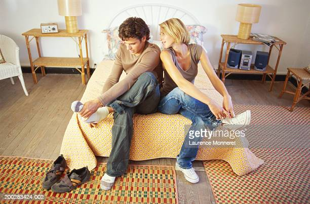 Young couple sitting on bed putting shoes and socks on