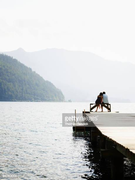Young couple sitting on bench at end of dock