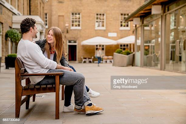 Young couple sitting on bench chatting, Kings Road, London, UK