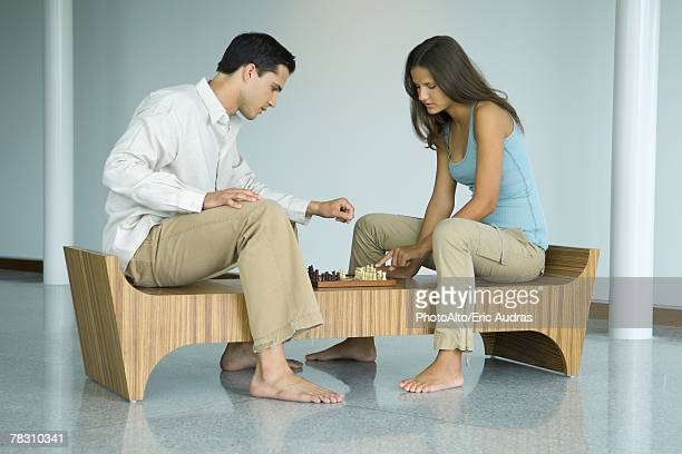Young couple sitting on bench, looking down at chess board together