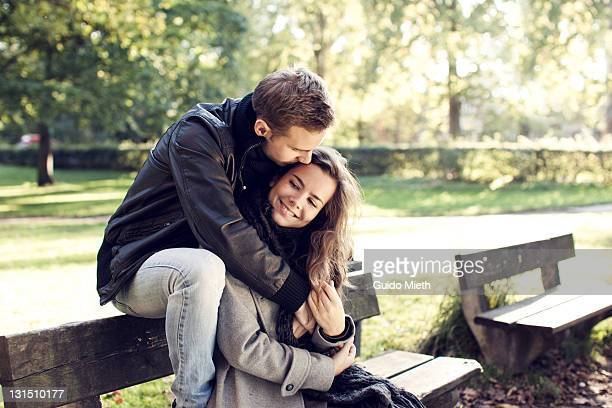 young couple sitting on bench outdoor. - verliefd worden stockfoto's en -beelden