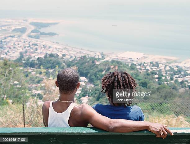 Young couple sitting on bench overlooking coast, rear view