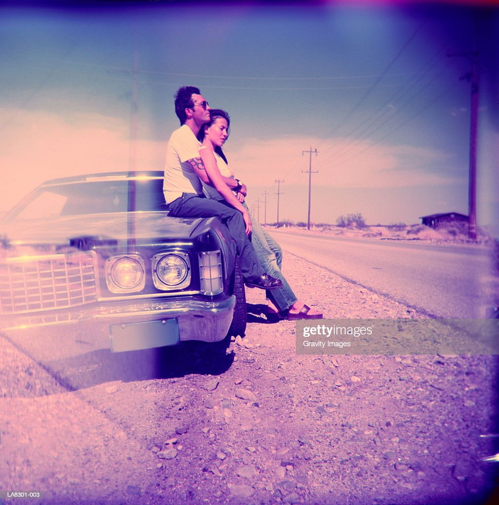 Young couple sitting on car (multiple exposure) : Stock Photo