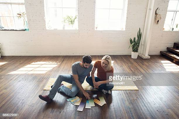 young couple sitting on carpet in a loft looking at color samples - home improvement stock pictures, royalty-free photos & images