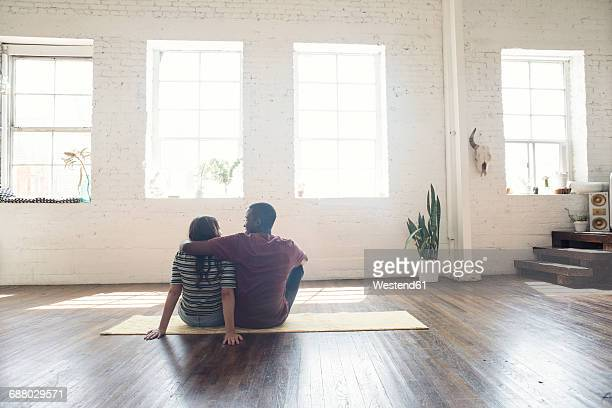 young couple sitting on carpet in a loft - new home stock pictures, royalty-free photos & images
