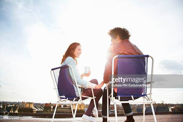 Young couple sitting on chairs on roof terrace