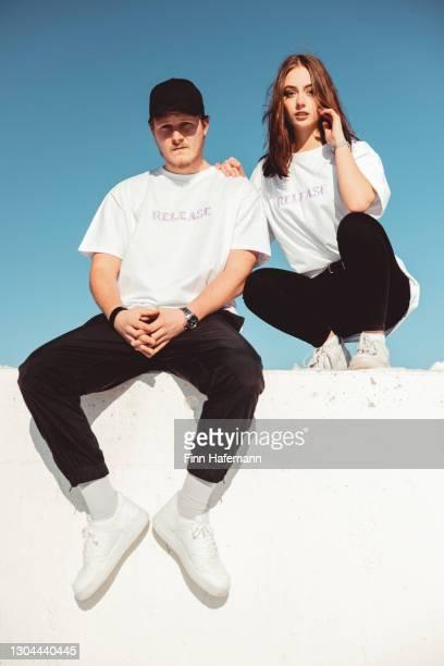 jovem casal sentado na parede de concreto - retrato de moda urbana moderna - coleção de moda - fotografias e filmes do acervo