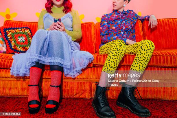 young couple sitting on couch - noapologiescollection stock pictures, royalty-free photos & images