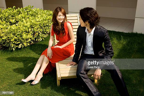 Young couple sitting on deck chair, relaxing, high angle