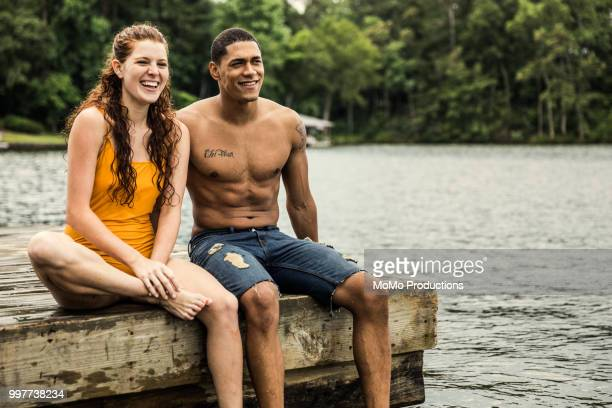 young couple sitting dock at lake