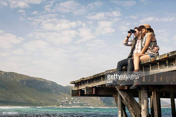 Young couple sitting on edge of old pier looking through binoculars, Cape Town, Western Cape, South Africa