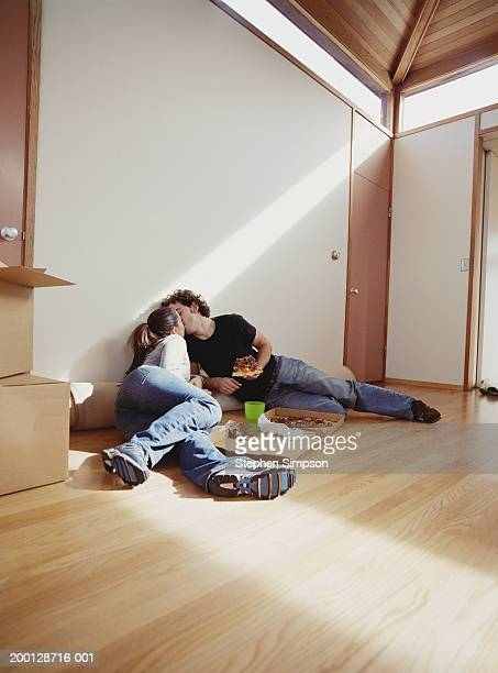 Young couple sitting on floor eating pizza, kissing