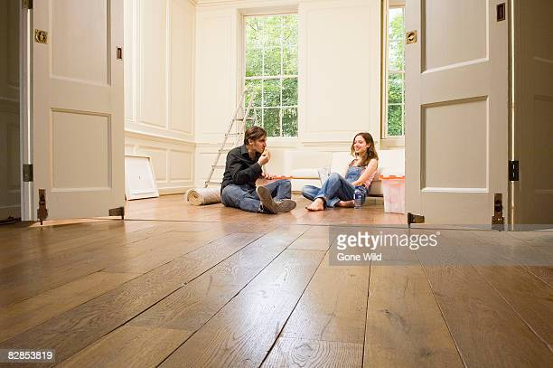 Young couple sitting on floor in e