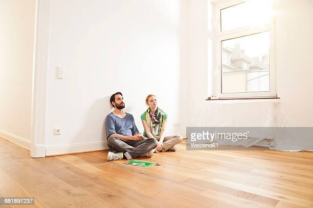 Young couple sitting on floor in empty apartment