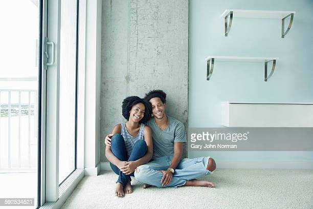 Young couple sitting on floor of new apartment