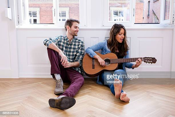 young couple sitting on floor with woman playing guitar - plucking an instrument stock pictures, royalty-free photos & images