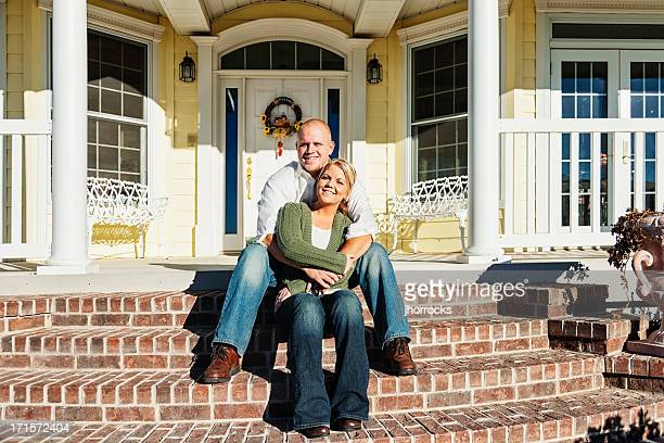 Young Couple Sitting on Front Steps of Their Home