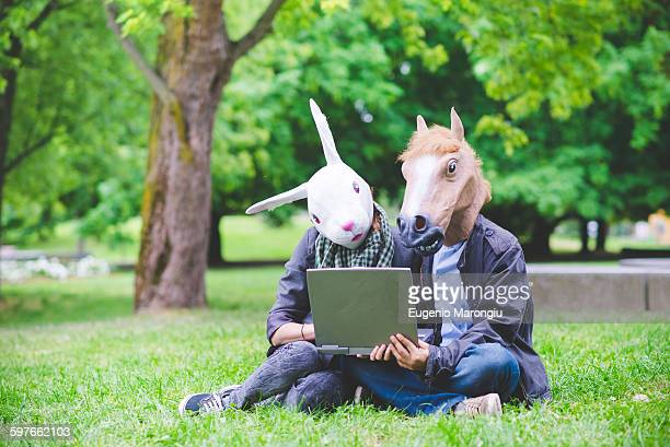 Young couple sitting on grass wearing rabbit and horse costume masks holding laptop computer