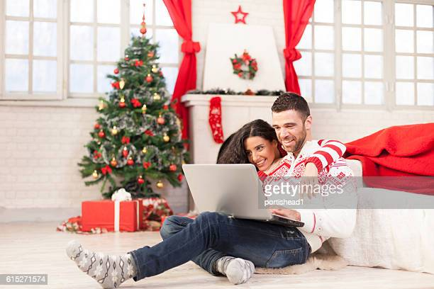 Young couple sitting on ground and using laptop
