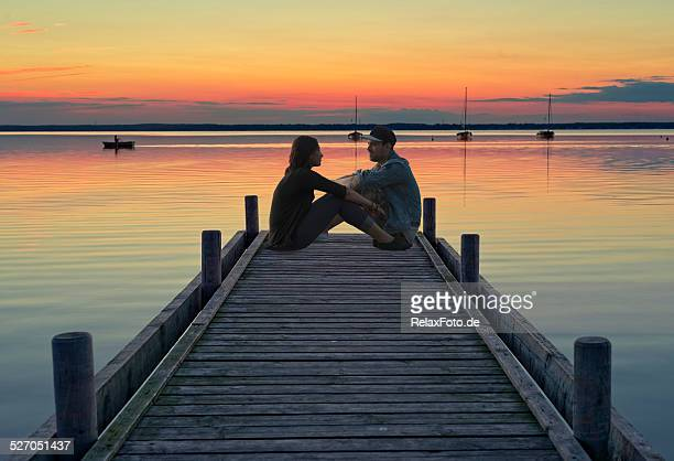 Junges Paar sitzt auf dem Anlegesteg bei Sonnenuntergang