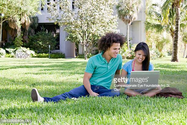 young couple sitting on lawn, using laptop and smiling - cef - fotografias e filmes do acervo