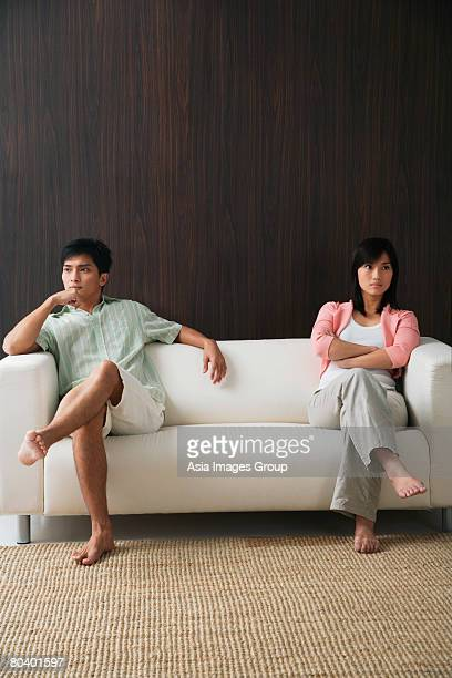 Young couple sitting on opposite ends of the sofa