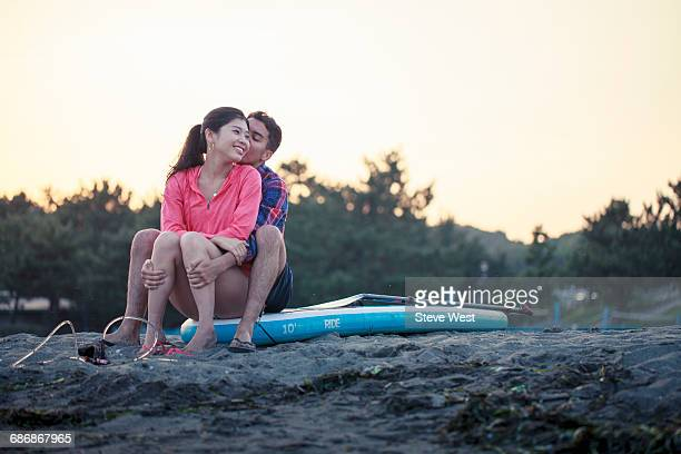 Young Couple Sitting On Paddleboard At Sunset
