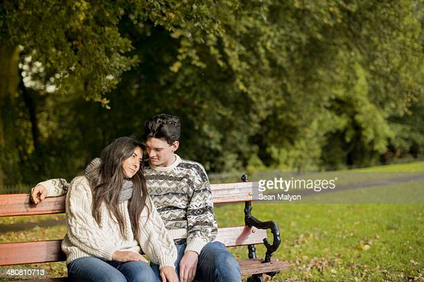 young couple sitting on park bench - sean malyon stock pictures, royalty-free photos & images
