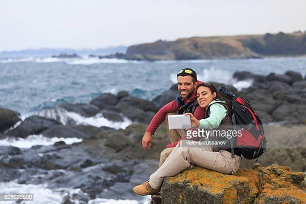Junges Paar sitzen auf Rock mit Digitaltablett