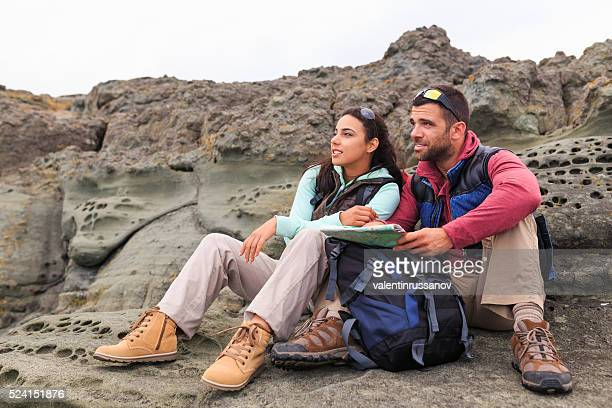 Young couple sitting on rocks and holding a map