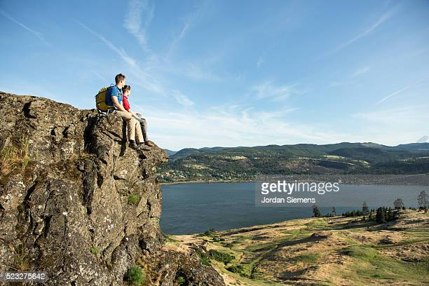 Young couple sitting on rocky mountain and admiring view, Oregon, USA