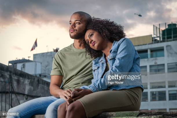 young couple sitting on rooftop - love at first sight stock pictures, royalty-free photos & images