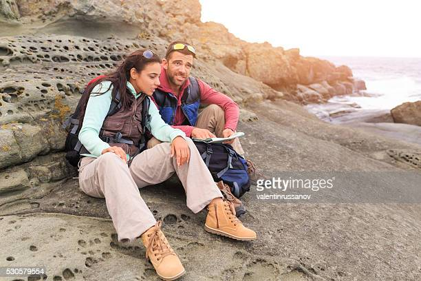 Young couple sitting on sand looking at map