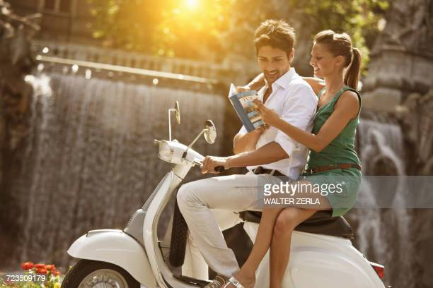 young couple sitting on scooter, looking at guidebook, turin, piedmont, italy - moped stock photos and pictures