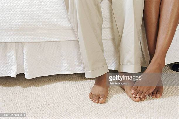 young couple sitting on side of bed, low section, close-up - black men feet stock photos and pictures